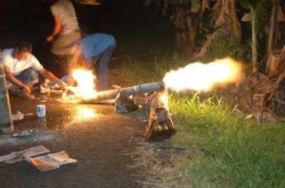 Image of a man in a remote area setting a bamboo cannon on fire