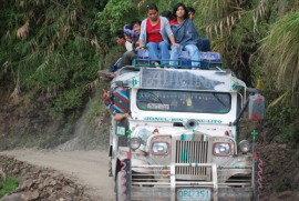 Image of a jeepney coasting along un unpaved road
